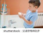 a little boy washes his hands... | Shutterstock . vector #1185984019