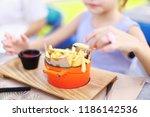 little girl eating fried...   Shutterstock . vector #1186142536