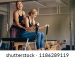 Small photo of Laughing female trainer helping a woman in pulling stretch bands sitting on pilates training machine. Smiling woman at the gym doing pilates training with her trainer.