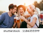 friends drinking beer and... | Shutterstock . vector #1186355599