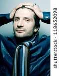 Portrait of a fashionable handsome man in blue jacket with striped scarf over light blue background holding his head. studio shot - stock photo