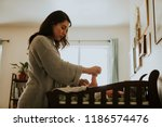 mother changing a diaper on a... | Shutterstock . vector #1186574476