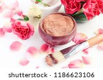 Stock photo ceramic bowl of red cosmetic clay for beauty treatment pink rose petals aroma oil skin care 1186623106