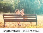 kids sitting on a bench in... | Shutterstock . vector #1186756963