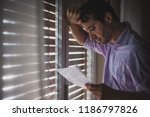 sad man reading a letter with... | Shutterstock . vector #1186797826