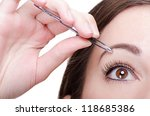 young woman tweezing her... | Shutterstock . vector #118685386