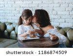 girl with her mother eats... | Shutterstock . vector #1186874509