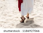 Small photo of cropped image of Jesus in robe, sandals and red sash walking on sand in desert