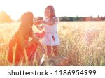 young girl in a wheat field.... | Shutterstock . vector #1186954999
