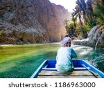 Small photo of Wadi Shab, Oman - Jan 2012: An old Omani man steers a boat across the shallow green water at the entrance to Wadi Shab, a beautiful scenic canyon near Muscat in Oman