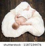 baby lying on white soft duvet... | Shutterstock . vector #1187234476