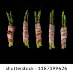 Sticks of green asparagus wrapped with bacon prosciutto ham over on black background. Overhad. Top view.