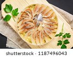 Stock photo marinated herring in oil on a wooden board on a gray dark table snack top view copy space 1187496043