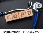 Small photo of Wooden block form the word COPD (Chronic obstructive pulmonary disease) with stethoscope. Medical concept.