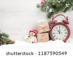 Small photo of Christmas gift boxes, alarm clock and fir tree branch covered by snow in front of wooden wall. With copy space for your greetings