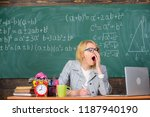 Small photo of Woman tired teacher sit table classroom chalkboard background. Working conditions for teachers. Work far beyond the actual school day. Working conditions which prospective teachers must consider.