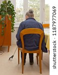 Small photo of Rear view of an old woman sitting at a table picking up something, that has fallen on the floor, with a long-reach grabber device for elderly or disabled people.