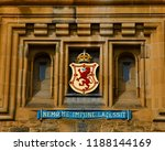 Small photo of Edinburgh castle entrance gatehouse slogan Nemo Me Impune Lacessit latin Motto on brown wall, royal coat of arms of Scotland