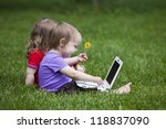 Two little children working together on the meadow with a laptop. - stock photo