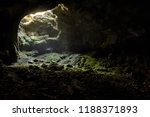 Small photo of Dark cave with a bright daylight spot of exit. Natural cave opening in Crimea. Entrance to the karst cave in a mountain. Inside the subterranean cave background with copy space.