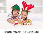 Happy christmas kids with elf and reindeer hats holding decorated gingerbread people - stock photo