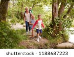 Family Hiking Along Path By...