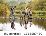 family crossing river whilst... | Shutterstock . vector #1188687490