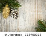Christmas golden balls and pine cone on spruce branch with wooden background - stock photo