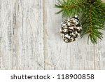 Golden Christmas pine cone on tree branch with wooden background - stock photo