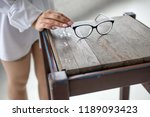 the woman's hand takes glasses... | Shutterstock . vector #1189093423