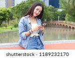 woman play mobile phone in park ... | Shutterstock . vector #1189232170