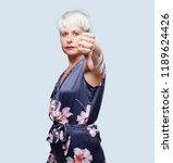 Small photo of senior cool woman with a dissenting, serious, stern expression, with thumbs down in disapproval.