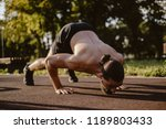 Small photo of Bearded man doing dive bomber push ups in outdoor gym with face down on a sunny day