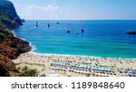 Small photo of Top aerial view from above of paradise beach resort in Alanya, Turkey, with gold sand, azure blue water of Mediterranean sea with ships, palms, rows of chaise lounges with colorful sun umbrellas