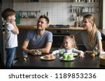 Stock photo little boy telling story poems standing on chair at breakfast mother father daughter listening 1189853236