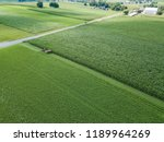 Small photo of An amish farmer and his four horse plow team plow a corn field seen from an aerial drone