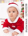 Curious baby girl in christmas outfit - closeup - stock photo