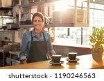 Stock photo smiling waitress wearing black apron standing behind counter in cafeteria and looking at camera 1190246563