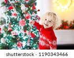 child decorating christmas tree ... | Shutterstock . vector #1190343466