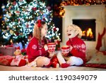 child under christmas tree at... | Shutterstock . vector #1190349079