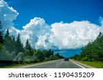 fluffy clouds over highway.... | Shutterstock . vector #1190435209