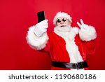 Stylish trendy grandfather aged mature Santa tradition winter costume headwear spectacles white beard take christmastime selfie picture front camera show v-sign isolated red noel eve background - stock photo