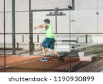 man playing padel in a orange... | Shutterstock . vector #1190930899
