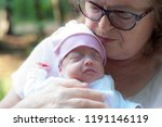 grandmother holds a small... | Shutterstock . vector #1191146119