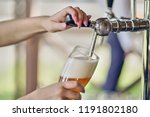 a barman pours beer into a... | Shutterstock . vector #1191802180