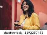 Small photo of Happy girl in hipster eyeglasses listening to music while going to work, cheerful hispanic woman drinking coffee outdoors using modern smartphone device, happy smiling european businesswoman walking