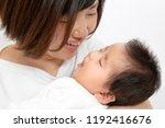 a mother staring at a newborn... | Shutterstock . vector #1192416676