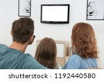 family watching tv in room at... | Shutterstock . vector #1192440580