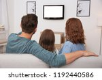 family watching tv in room at... | Shutterstock . vector #1192440586