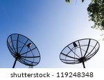 Old double satellite dishes with twilight blue sky and trees background - stock photo
